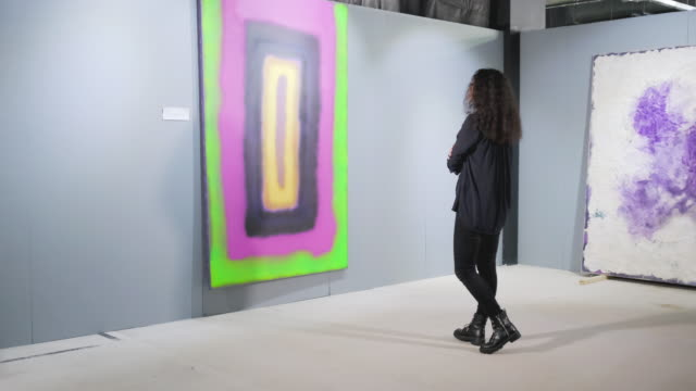 Woman peering into the painting at art gallery