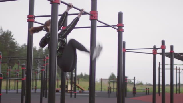 woman performing toe to bar leg raises at outdoor fitness court - dito del piede video stock e b–roll