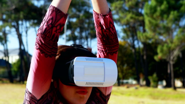 Woman performing yoga while using virtual reality headset 4k video