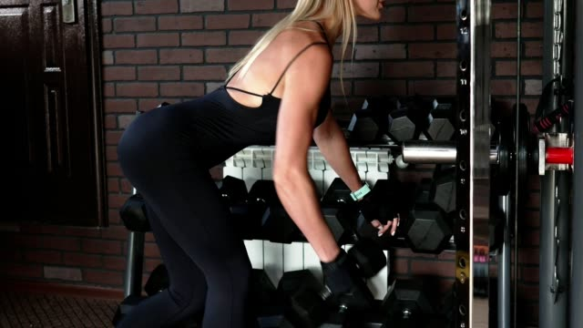 Woman performs one arm bent-over dumbbell row exercise Woman athlete performs one arm bent-over dumbbell row exercise in the gym human back stock videos & royalty-free footage