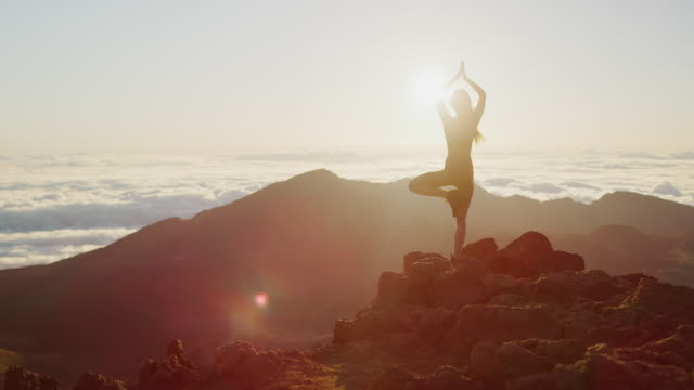 Woman performs yoga pose at sunrise