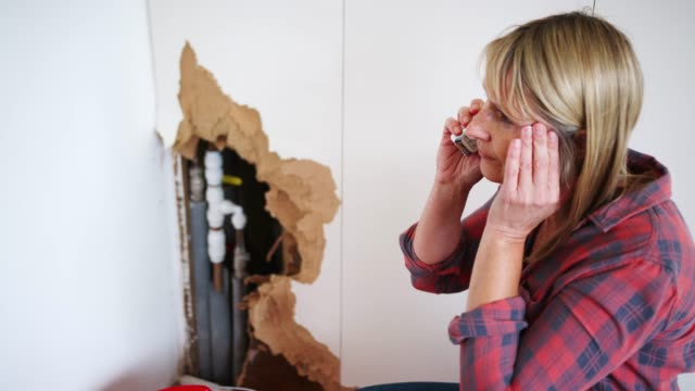 Woman Phoning Emergency Plumber After Water Leak At Home