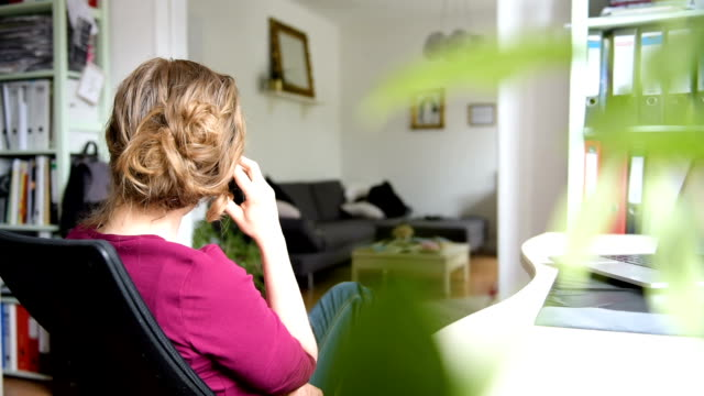 Woman phoning with a telephone from home at an office desk in the living room. The video is filmed out of a rear view by looking in the domestic room. landline phone stock videos & royalty-free footage