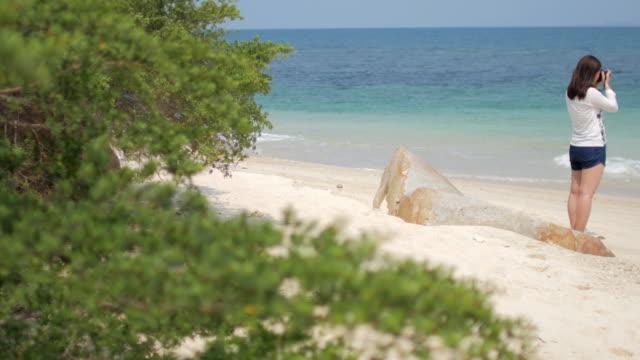 Woman photographer take a photo on the beach , sea summer concept , 4k(UHD) video