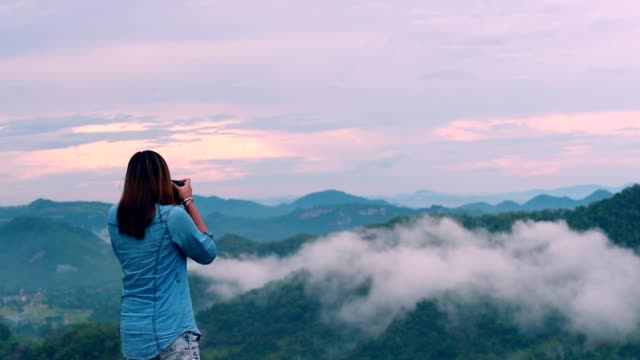 Woman photographer taking photo at mountain, Slow motion video