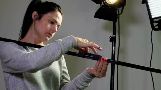 Woman photographer with camera slider near near LED fresnel and LED panel lights - vídeo