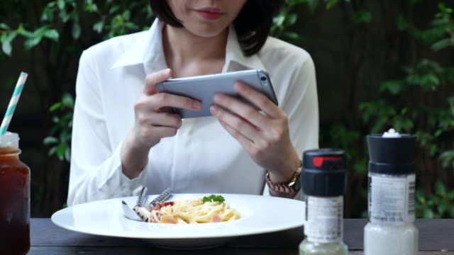 Woman photographing food of Spaghetti in restaurant video