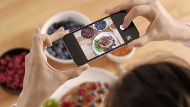 frau fotografieren ihr frühstück in der küche - bloggen stock-videos und b-roll-filmmaterial