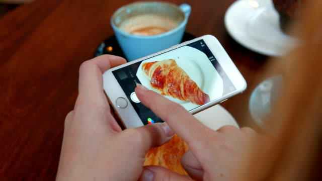 Woman photographing her croissant on smartphone video
