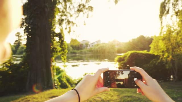 vidéos et rushes de femme de photographier le coucher du soleil. - photophone