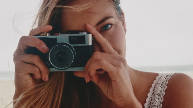 Woman photographing through camera at beach