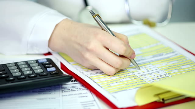 Woman physician filling out papers, calculating patient's health insurance costs