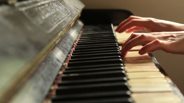 vídeos de stock e filmes b-roll de woman pianist at the rusty piano keys, arms plays solo of music - compositor