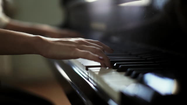 Woman pianist close-up two hands plays energetic classical music on grand piano