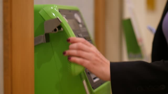 Woman pick up handset and push buttons on public payphone, close up shot Woman pick up handset and push buttons on public payphone, close up shot with selective focus. Green colored telephone device, modern phone at Japan telephone receiver stock videos & royalty-free footage