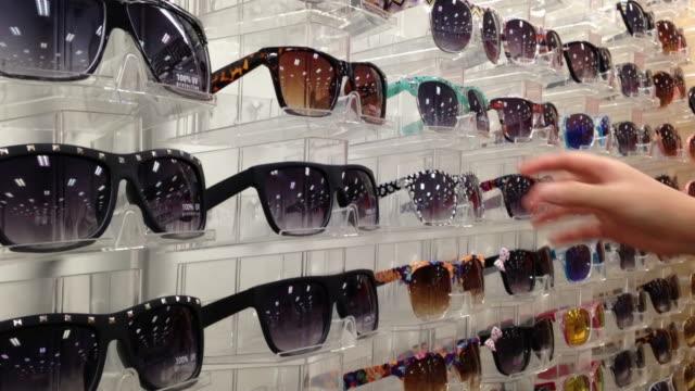 frau abholen eine sonnenbrille - sonnenbrille stock-videos und b-roll-filmmaterial