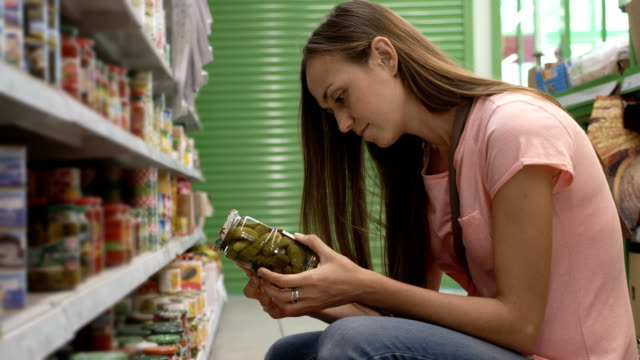 vídeos de stock e filmes b-roll de woman picking canned food from the shelves at supermarket and reading the label - ingrediente
