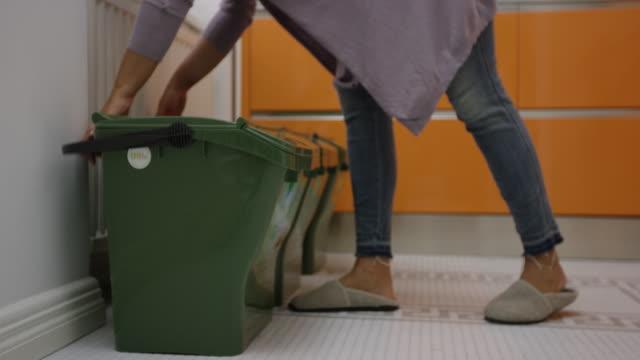 vídeos de stock e filmes b-roll de woman picking up recycling bins and taking out the trash - economia circular