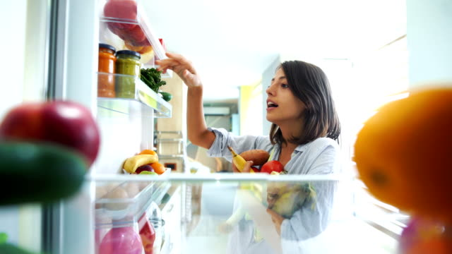 Woman picking up some fruits and veggies from the fridge timelapse. Timelapse closeup of a cheerful young couple picking some fruit and veggies from the fridge to make some healthy breakfast on Sunday morning. Shot from inside the working fridge. fridge stock videos & royalty-free footage
