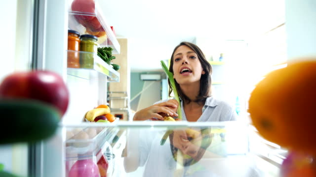 Woman picking up some fruits and veggies from the fridge. Closeup of a cheerful young couple picking some fruit and veggies from the fridge to make some healthy breakfast on Sunday morning. Shot from inside the working fridge. fridge stock videos & royalty-free footage