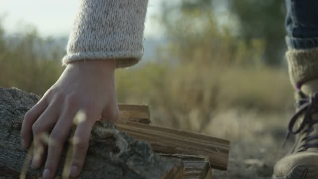 A Woman Picks Up Firewood in the Desert A woman in a cream-colored sweater and boots picks up a piece of cut firewood outdoors at sunset. firewood stock videos & royalty-free footage