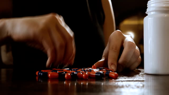 Woman piking up pills from table surface video