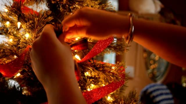 vídeos de stock, filmes e b-roll de mulher coloca um laço em uma árvore de natal em torno dos feriados alt - decoração