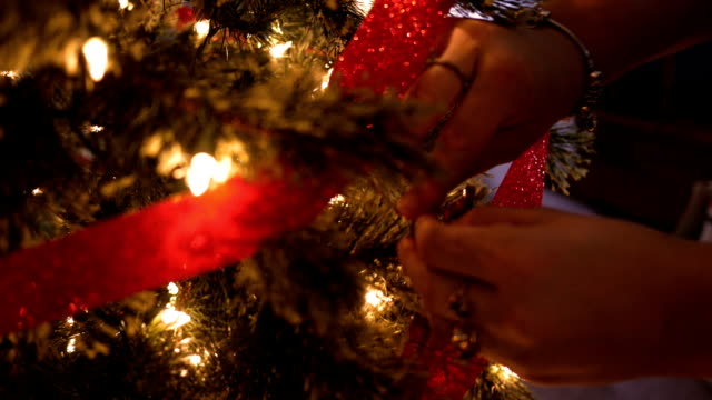 Woman places a bow tie on a Christmas tree around the holidays video