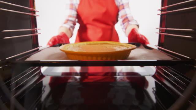 woman places baking sheet with pumpkin pie into the oven - nadziewany placek filmów i materiałów b-roll