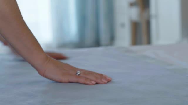 vídeos y material grabado en eventos de stock de mujer puesta una bata de baño limpia y fresca en una cama de hotel - montar