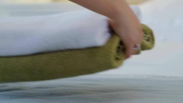 Frau eine saubere, frische Handtücher auf einem Bett platzieren und dann glätten es mit ihren Händen – Video