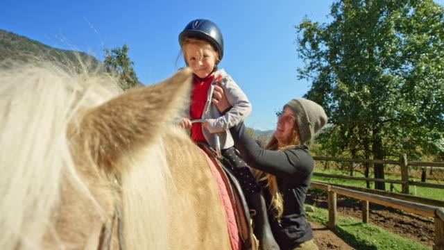 女性馬の日差しの中でバックに小さな女の子を配置します。 - スポーツ用品点の映像素材/bロール