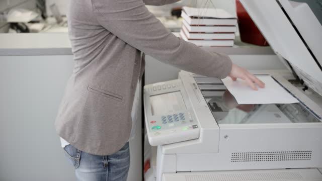vídeos y material grabado en eventos de stock de mujer, colocar una hoja de papel en la máquina duplicadora - copiar