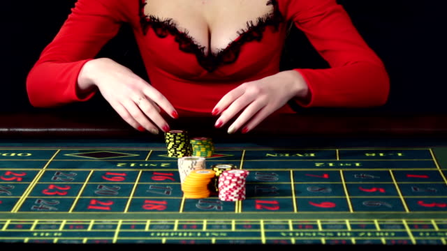 Woman placing an all in bet in roulette. Black video