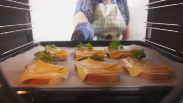kvinna att placera ost rostat bröd på en plåt i ugnen - cheese sandwich bildbanksvideor och videomaterial från bakom kulisserna