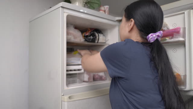 Woman placing frozen food in freezer of refrigerator Woman placing frozen food in freezer of refrigerator in quarantine Curfew days. freezer stock videos & royalty-free footage