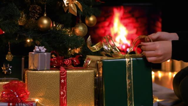 kvinna placera gåvor under julgran nära eldstad - christmas presents bildbanksvideor och videomaterial från bakom kulisserna