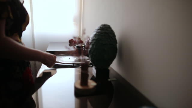 Woman Placing The Stylus Needle On Vinyl Record to Play Some Music
