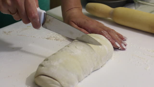 a woman plans with a knife rolled into a roll dough for cinnabons. nearby are cooking tools. - formare pane video stock e b–roll