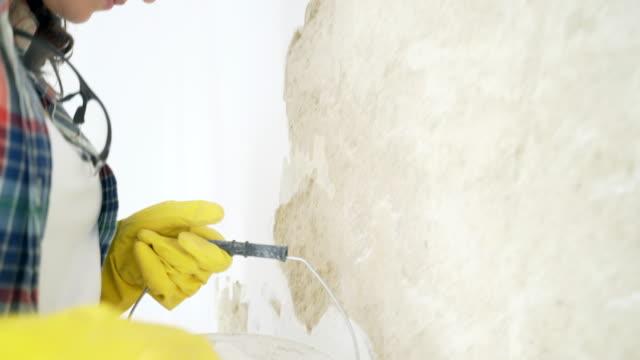 女性は彼女の家のパレットで壁を左官工事します。 - セメント点の映像素材/bロール