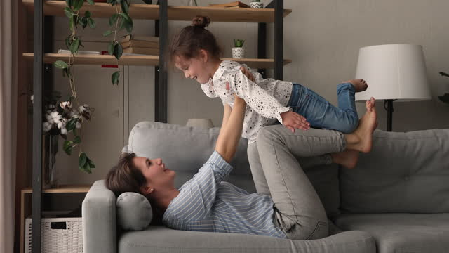 Woman play with daughter lying on sofa in living room