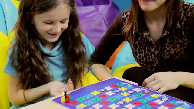 vídeos y material grabado en eventos de stock de mujer sonriente niña jugando a las cartas de juego, madre enseñanza niño - tablón