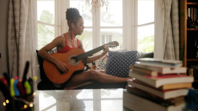 Woman Playing Classic Guitar And Singing In Her Room Black girl lying on couch and singing song, young african american woman relaxing. Happy latina sitting on sofa and playing guitar. Hispanic people and lifestyle. Music, leisure and relaxation at home guitar stock videos & royalty-free footage