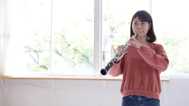 A woman playing oboe