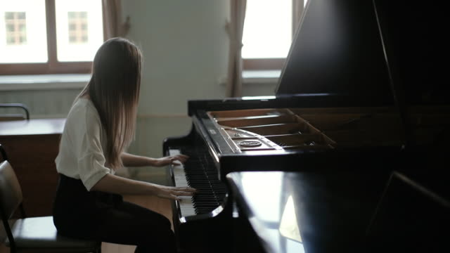 Woman playing the black piano on the background of the window in slow motion
