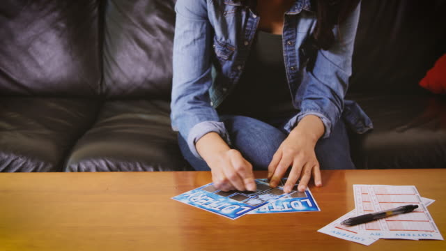 woman playing the lottery - lotteria video stock e b–roll