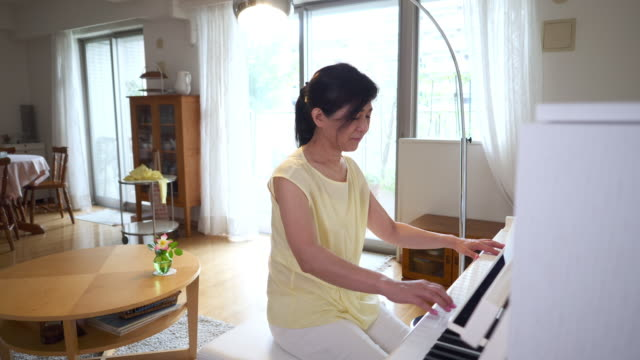 Woman playing the piano in living room