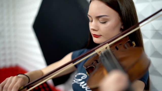 Woman playing violin in recording studio