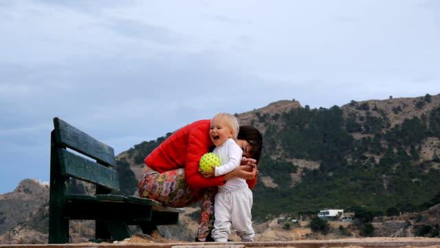 kadın dağ zemin üzerine bir bebekle oynarken. bankta oturan genç beyaz anne gülmek sarışın sevimli bebek yapar. sivilce ile sarı lastik bir top tutan bebeğim. - mountain top stok videoları ve detay görüntü çekimi