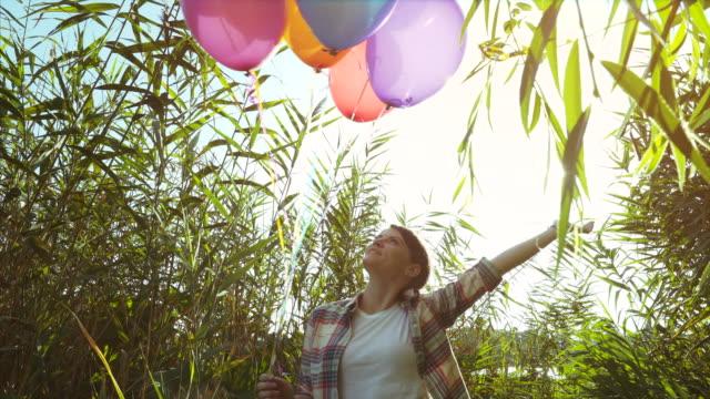 vídeos de stock, filmes e b-roll de mulher jogando com um monte de balões. - punhado